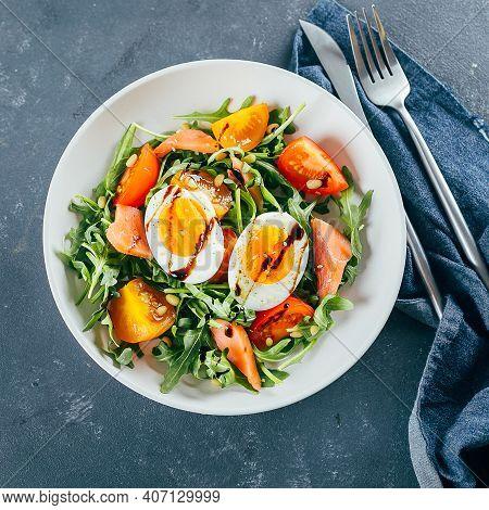 Healthy Vegan Salad Of Fresh Tomato, Arugula, Salmon, Egg And Sesame On Plate. Diet Menu. Top View.