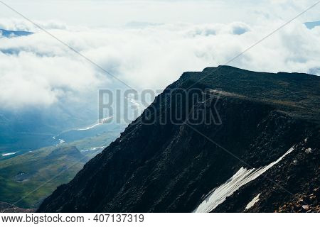 Awesome Landscape With High Black Cliff Among Low Clouds. Dark Mountain Of Rough Black Stones And Se