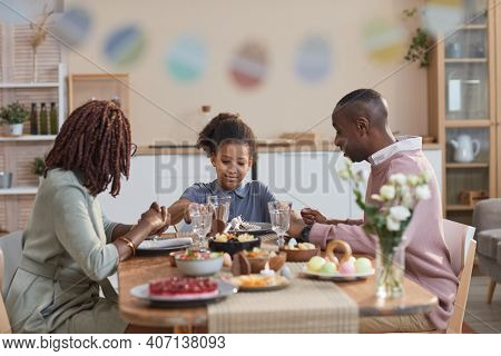 Portrait Of Modern African -american Family Enjoying Dinner Together While Celebrating Easter At Hom