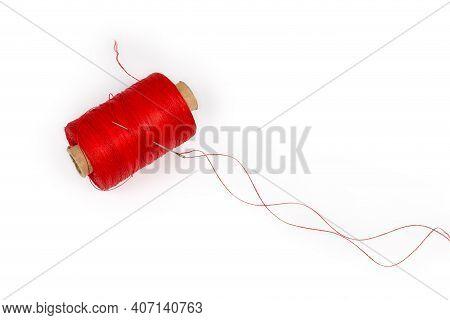 Self-threading Hand Sewing Needle With A Red Thread Tucked Into It Is Stuck Into The Spool Of The Sa