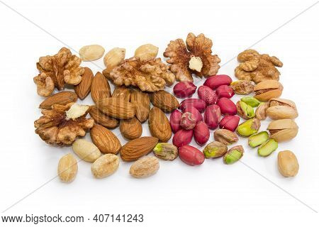 Kernels Of The Various Nuts Peeled From Shells And Some Pistachio In Shells Scattered On A White Bac
