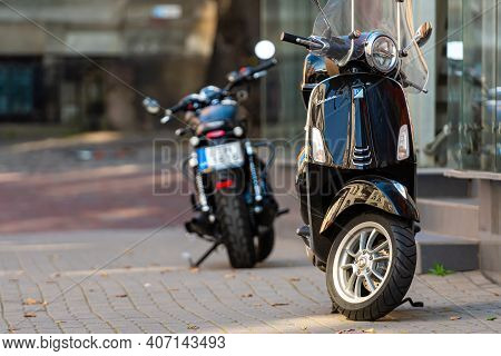 Riga, Latvia - October 7, 2020: Vespa Scooter And Motorcycle Parked On The Pavement Of The Old Town