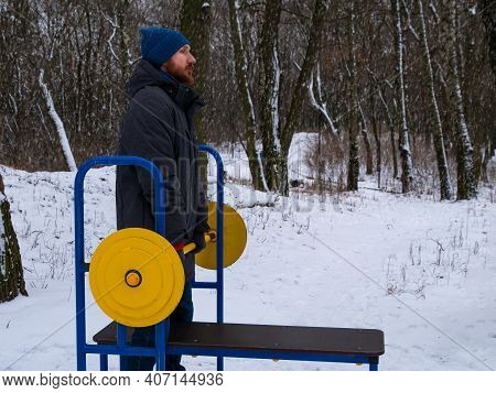 Athletic Man Bodybuilder Training Lifting Barbell Outdoors On Winter Day. Bearded Guy Doing Strength