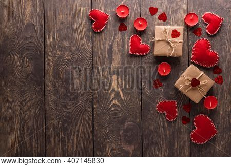 Romantic Image For Valentine's Day Red Hearts, Candles And Bright Gifts On A Wooden Background