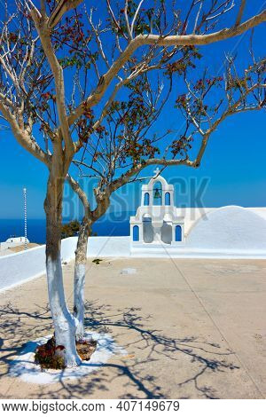 View of square in Oia town with small belfry in Santorini, Greece