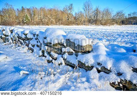 Stonewall Covered In Snow Near Agriculture Field