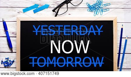 Yesterday Now Tomorrow Written On A Black Note-board Next To Blue Paper Clips, Pencils And A Pen.