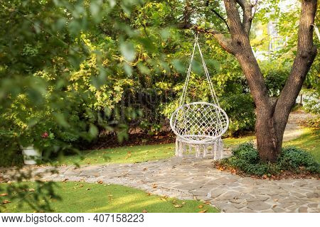 Comfortable Hanging Wicker White Chair In Summer Garden. Cozy Hygge Place For Weekend Relax In Garde