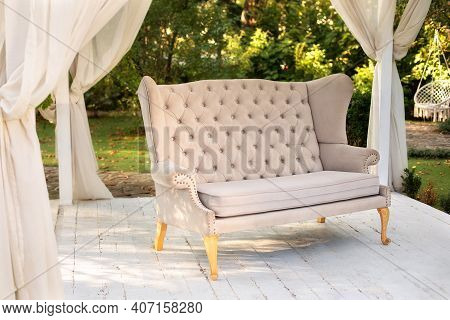 Elegant Sofa In The Garden. In Garden There Is Podium On Which Sofa. Summer Gazebo With Flowing Whit