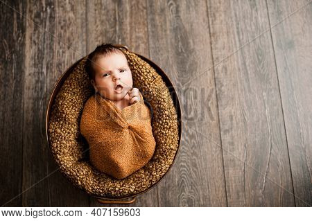 3. Baby Girl In A Brown Wrap Is Yawning At A Newborn Photoshoot