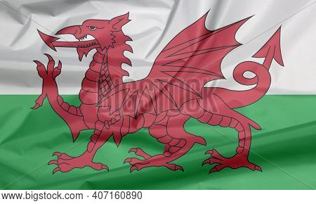 Fabric Flag Of Wales. Crease Of Wales Flag Background, Consists Of A Red Dragon Passant On A Green A