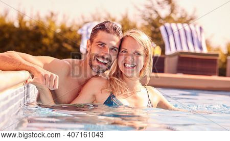Portrait Of Couple Having Fun On Summer Vacation Relaxing In Outdoor Swimming Pool