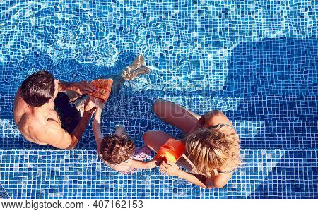 Overhead Shot Of Family With Young Son Putting On Armbands For Swimming Lesson In Outdoor Pool
