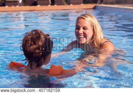 Mother And Son In Outdoor Pool On Summer Vacation Teaching Son To Swim With Inflatable Armbands