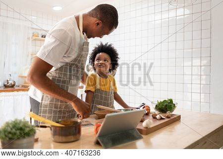 Happy Black Family. African American Father And Little Son Doing Online Cooking With Digital Tablet