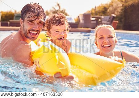 Family With Young Son Having Fun With Inflatable On Summer Vacation In Outdoor Swimming Pool
