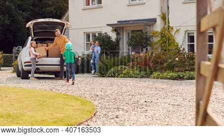 Family Outside New Home On Moving Day Unloading Boxes From Car As Son With Skateboard Runs To Help