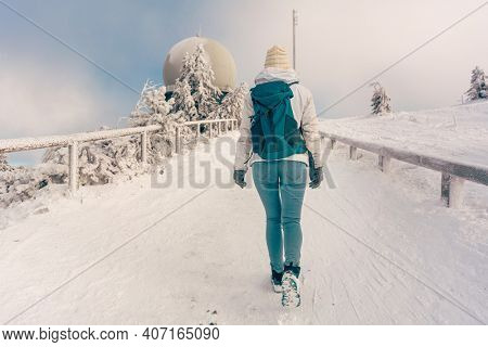 Winter hike at the peak of the Grosser Arber mountain with woman walking up a path
