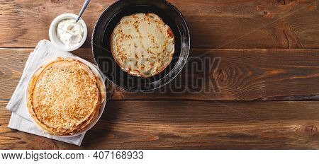 Traditional Russian Crepes Blini Stacked In A Plate And Pancake In Cast-iron Frying Pan On Wooden Ta