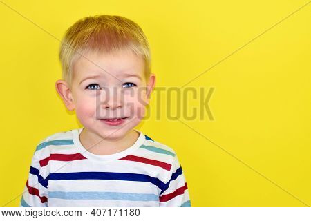 Close Up Portrait Of A Handsome Little Laughing Boy. Adorable Small Child Laughs On Yellow Backgroun