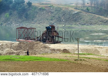 Gold Mining On The River Taedong, North Korea. Dredge On The River At Dawn
