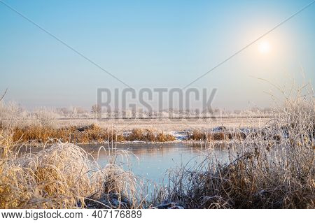 Sun Over The Winter Small Pond. Meadows, Bushes And Trees Covered With Frost. Fabulous Winter Landsc
