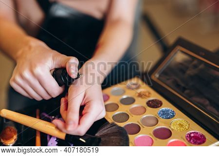 Close-up Of Hands And Make-up Concealer. Close-up Of Cosmetics, Eyeshadows, Brushes