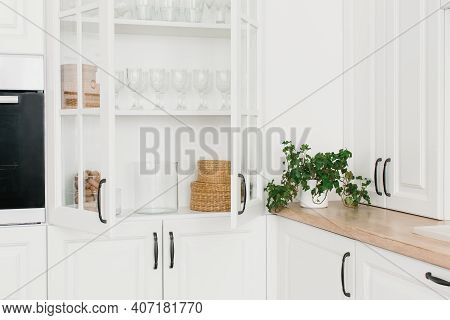 Opened White Glass Cabinet With Clean Dishes And Decor. Scandinavian Style Kitchen Interior. Organiz