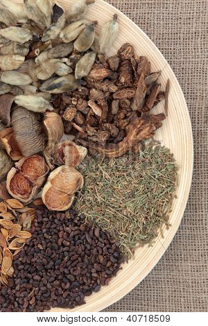 Chinese traditional herbal medicine selection on a round wooden bowl over hessian background.