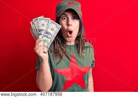 Woman wearing t-shirt with red star communist symbol holding bunch of dollars banknotes scared and amazed with open mouth for surprise, disbelief face