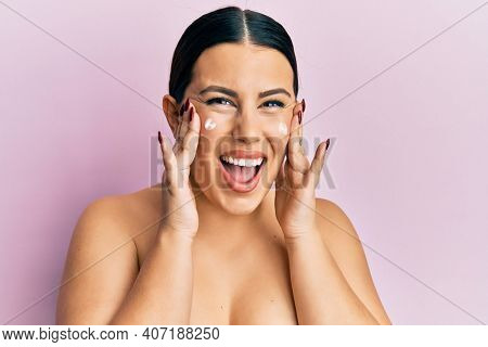 Beautiful brunette woman standing topless wearing face cream smiling and laughing hard out loud because funny crazy joke.