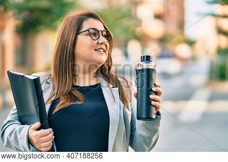 Young plus size businesswoman holding binder and bottle of water  at the city.