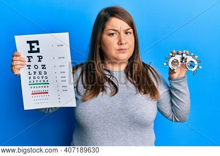 Beautiful brunette plus size woman holding optometry glasses and eyesight test skeptic and nervous, frowning upset because of problem. negative person.