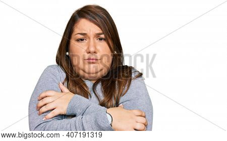 Beautiful brunette plus size woman wearing casual clothes shaking and freezing for winter cold with sad and shock expression on face