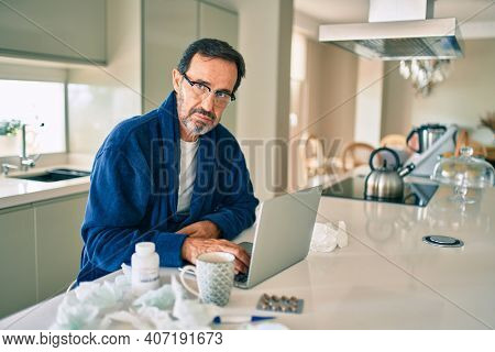Middle age man feeling sick with cold and fever at home, ill with flu disease working from home