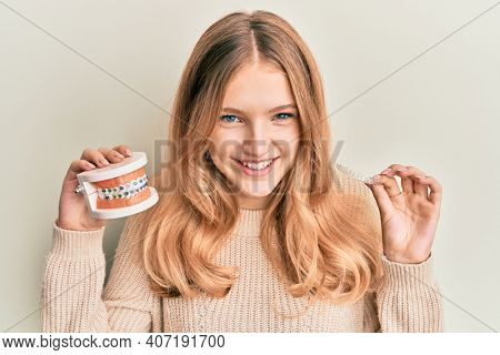 Beautiful young caucasian girl holding invisible aligner orthodontic and braces smiling and laughing hard out loud because funny crazy joke.