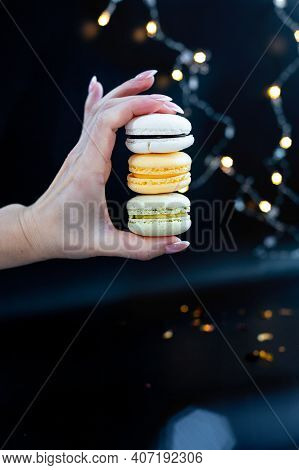 I Want Macaroons, Female Hand Holds Macaroons On Black Background