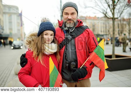 Father And Daughter Holding Lithuanian Flag On Lithuanian Independence Day In Vilnius. Happy Family