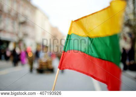 Lithuanian Flag Hold During Celebration Of Restoration Of The State Day In Vilnius. Bonfires Are Lit