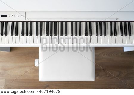 Piano Keyboard And Bench. Classical Music On Electronic Digital Piano. Flat Top View On Wood Floor.