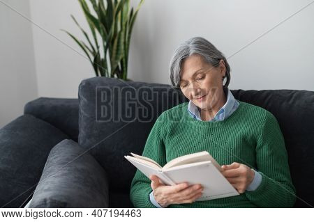Portrait Of A Charming Retired Senior Mature Lady Wearing Green Sweater Jumper And Reading An Intere