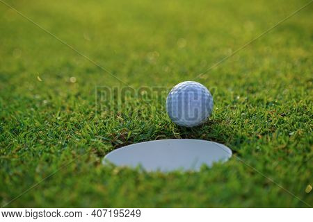 The Ball At The Hole On The Golf Course. Golf Ball Putting On Green Grass Near Hole Golf To Win In G