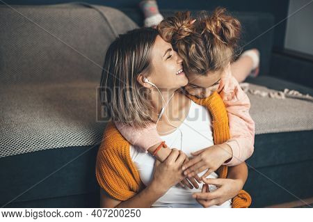 Caucasian Daughter Embracing Her Mom While She Is Listening Music On Earphones And Smile
