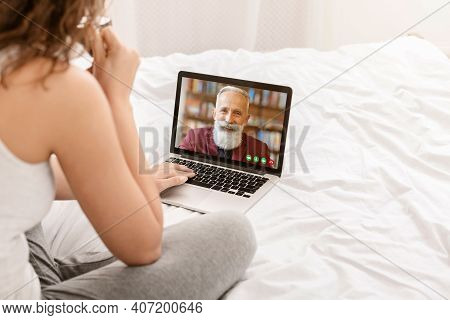 Young Woman Using Modern Laptop To Speak To Her Senior Father Screen On Bed At Home. Millennial Lady