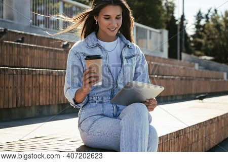Millennial Woman In Denim Clothes Sits On Park Bench, Holding A Smart Tablet In Her Hands. Woman Use