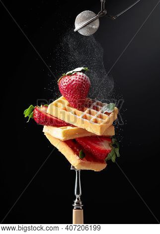 Waffles With Fresh Juicy Strawberries Sprinkled With Sugar Powder On A Black Background.