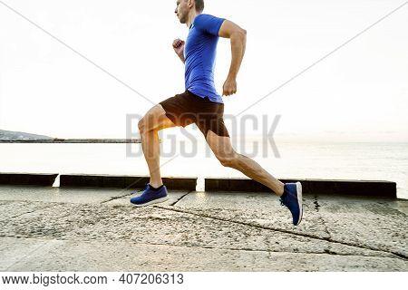 Male Runner Run In Morning Light Of Dawn Along Sea Embankment