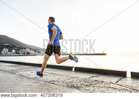 Man Runner Run In Morning Along Sea Embankment In City