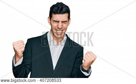 Handsome hispanic man wearing business clothes very happy and excited doing winner gesture with arms raised, smiling and screaming for success. celebration concept.