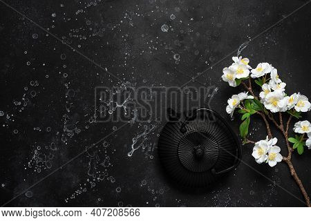 Asian Metal Teapot And Blossom Cherry Branch Artificial On A Black Stone Background. Black Cast Iron
